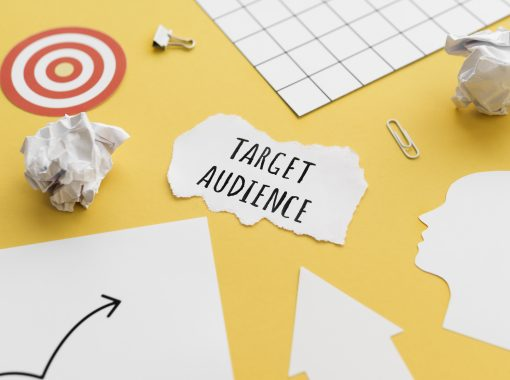 """""""Target Audience"""" is written on a scrap of paper on a yellow table top with other pieces of paper"""