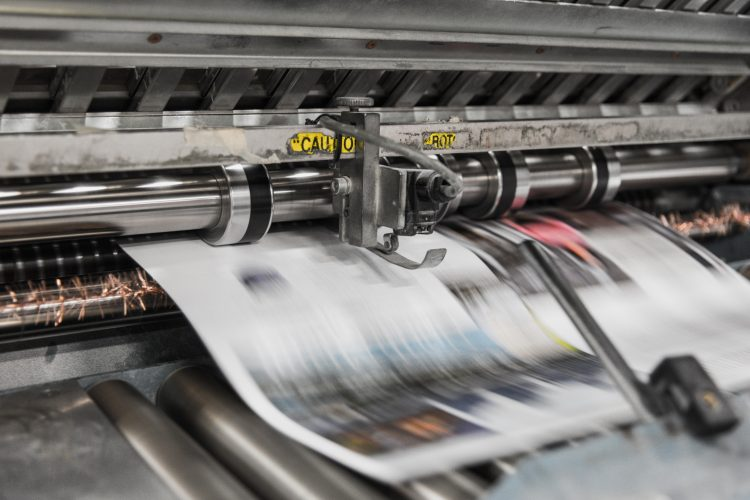 """Picture of newspapers being printed. Image is being used for a Newswire blog titled, """" The News Never Stops. Stand Out With Press Release Distribution Software."""""""