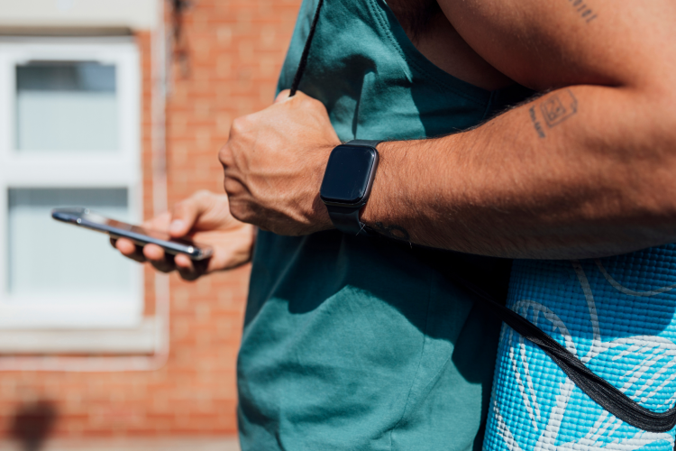 """Picture of a man in a blue shirt wearing fitness gear, reading his mobile phone. Image is used for blog titled, """"Newswire Helps Land Wall Street Journal Feature for Tech Industry Client"""""""