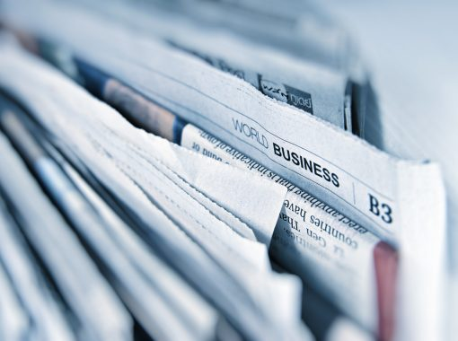 """Picture of newspapers and the focus of the picture is on the word, """"Business."""" Image is being used for a blog about earned media mentions for a health tech company."""