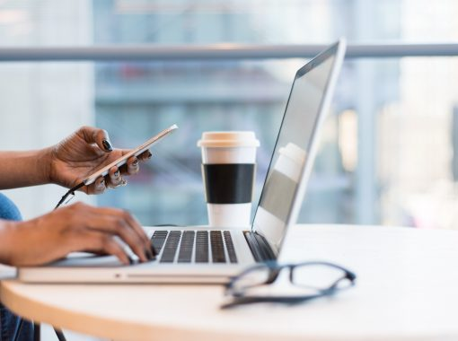 """Picture of woman typing on computer, looking at phone, with coffee cup near by. Picture being used for blog, """"Are Press Releases Driving Business Growth for CEOs?"""""""