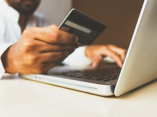 Picture of a person making a payment on their laptop, holding a credit card. Image is being used for a blog post about FeatherPay and healthcare payments.