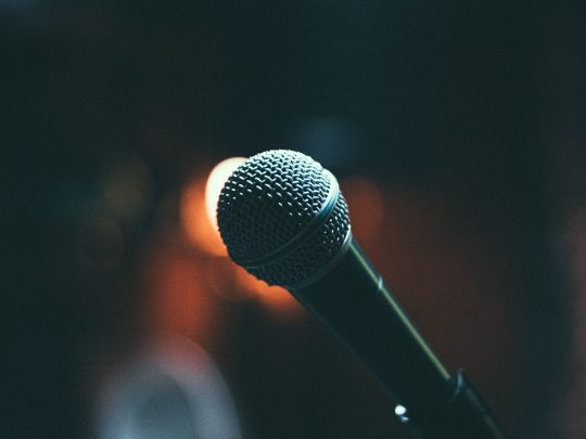 """Close-up picture of a microphone on stage. Image is being used for a blog post titled, """"How Are Small and Midsize Companies Using this Marketing Strategy to Amplify Messaging?"""""""